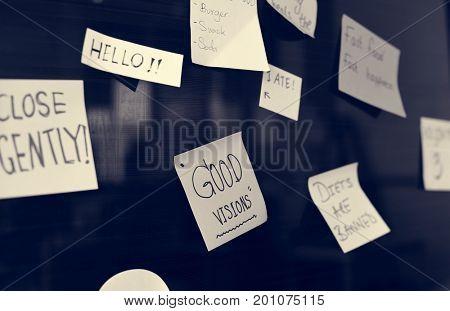 Sticky note reminder on bulletin board
