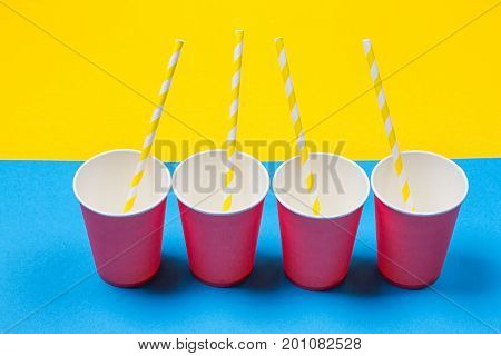 a bundle of multi-colored drinking straws in a paper Cup on a yellow and blue background. fashion minimal. flat lay