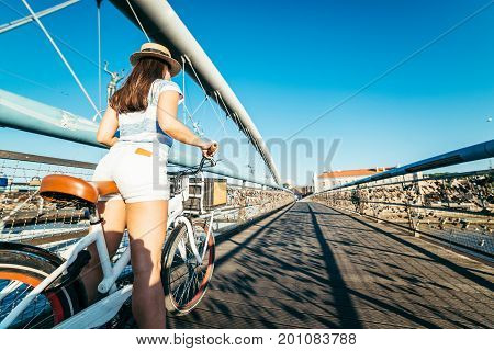 sexy woman stands with bicycle in the middle of the bridge on sunset