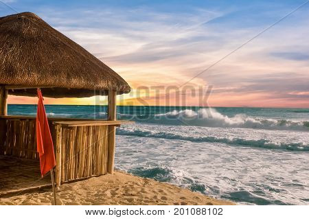 A bamboo and straw thatch hut on a sandy beach with rough seas and partly cloudy sky