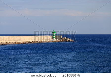 A green and white lighthouse on the end of a seawall in the harbor of Barcelona