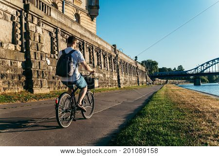 man riding bicycle at embankment of Wisla river at the sunset