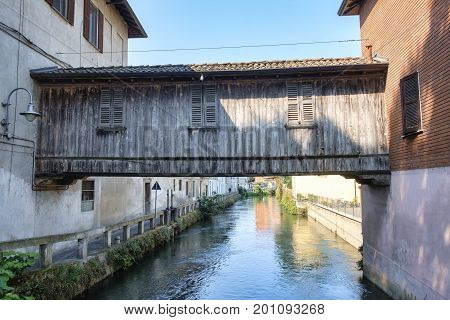 Gorgonzola (Milan Lombardy Italy): the canal of Martesana with historic buildings reflected in the water. The famous wooden bridge