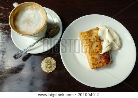 Capuccino, pancake with sour cream and bitcoin gold coin on the table in cafe. Payment by crypto currency concept