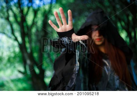 Photo of witch in black cloak with outstretched hand in forest