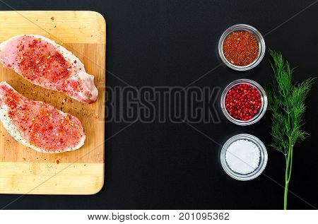 Pork loin on cutting board with various seasonings on dark background. Overhead food shots. Cooking. Copy space background