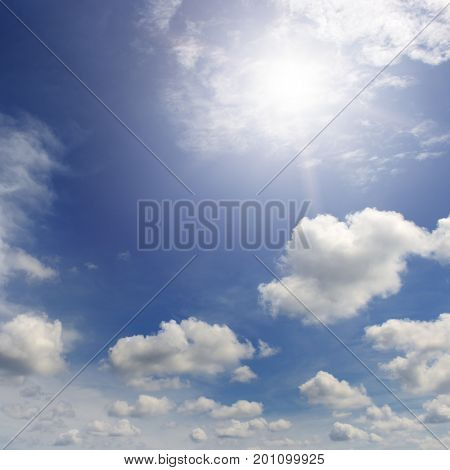 Bright sun in  blue sky amongst white clouds.