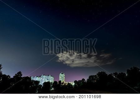 Starry night in a cloudy sky over the buildings of the city of Kiev in Ukraine