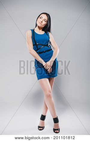 lifestyle, fashion and people concept: pretty smiling woman wearing dark blue dress and swordbelt, posing on white background