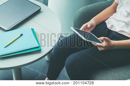 Close up hand of girl sitting and touch blank screen of tablet computer with notebook and pencil on table in campusOnline education (e-learning) conceptBlank screen for adding designclipping path.