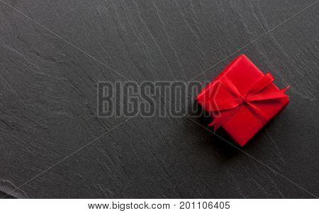 red beautiful wraped gift box on black background