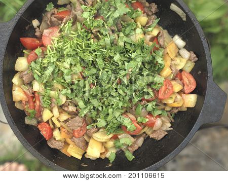 Cast Iron pot of ready to eat food with herbs on a top above view