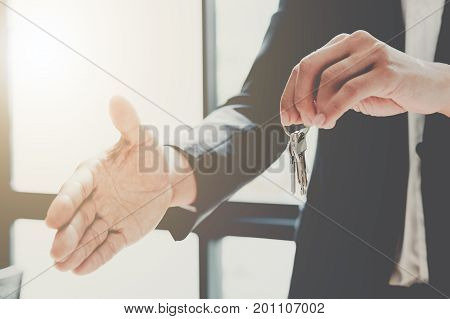 Real Estate Agent Handing Over House Keys With Approved Mortgage Application Form And Offer Handshak