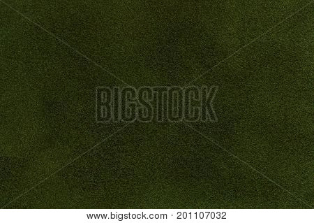 Background of dark green suede fabric closeup. Velvet matt texture of emerald nubuck textile.