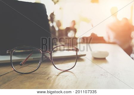 Close up of eye glasses on work desk with chart and laptop at business workplace with business people meeting background