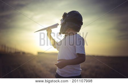 Imagination, Boy playing to be a classic pilot, wearing a fur hat, glasses and wings made of cardboard as a toy