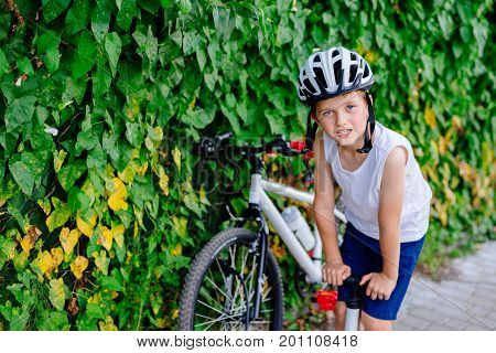 Boy Child In White Bicycle Helmet Inflating Tire
