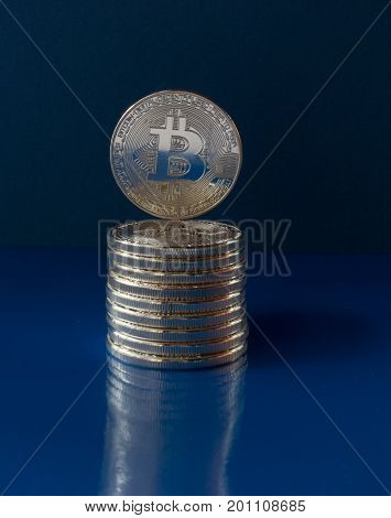 On a blue background are coins of a digital crypto currency - bitcoin. On the lying coins is one coin built. On the glass background is a reflection of coins.