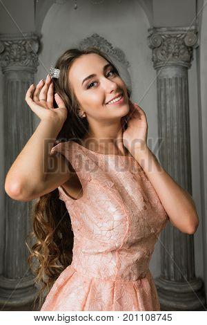 Portrait of Pretty romantic lady. Beautiful young woman in a pink lacy dress in a vintage luxury grey interior. long curly hair fashion makeup