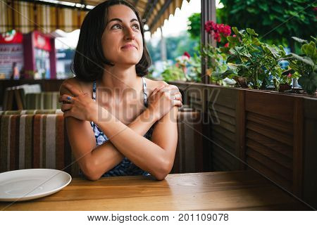 A Girl Is Waiting For Her Order In A Cafe.