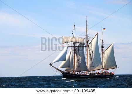 Sailing ship sailing at the dark sea under the blue sky.