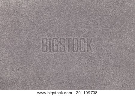 Background of light gray suede fabric closeup. Velvet matt texture of silver nubuck textile.