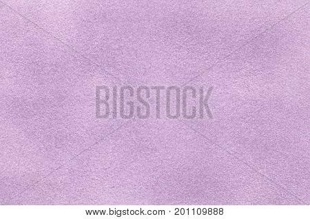 Background of light violet suede fabric closeup. Velvet matt texture of lilac nubuck textile.