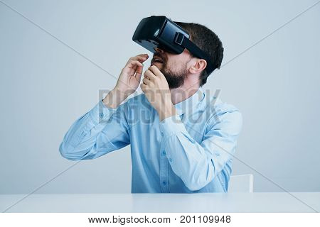 Young guy with a beard in virtual reality glasses.