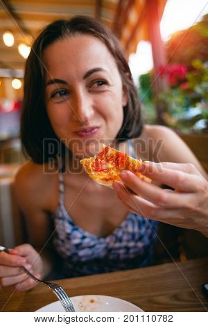 The Girl Is Eating Pizza.