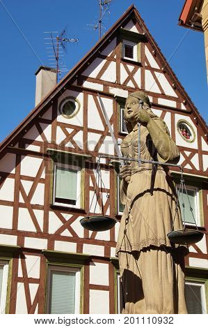 Scales Of Justice With In Background A Typical German House