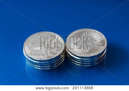 On a blue background are coins - It's the back and face of the coin of a fictitious crypto currency bitcoin.