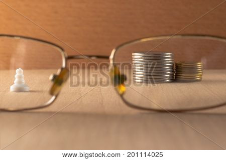Chess pawn and metal coins view through eye glasses on a wooden background