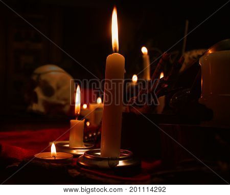 Burning candles and human skull. Halloween and occult concept.
