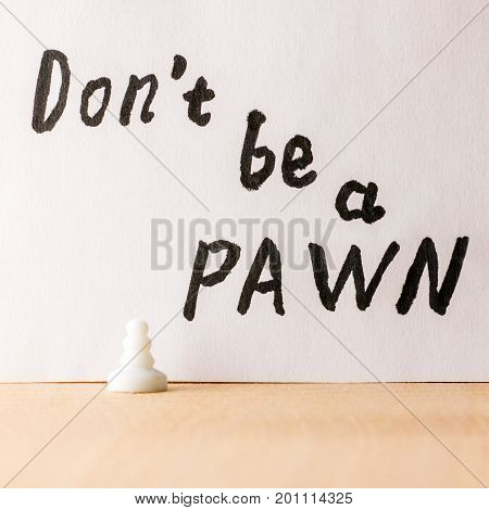 Do not be a pawn inscription in English under which stands a small chess piece symbolizing a person with a low status