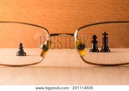 The pawn and the king with the queen through the eye glasses of the figure symbolize people from different social strata