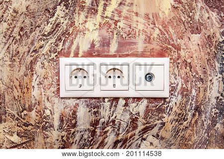 Double electrical socket with TV antenna socket on brown wall with abstract pattern