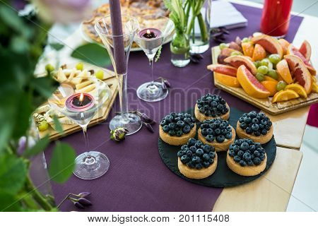 Blueberry tartlets on slate stone, plate with fruits, candles. Sweet dishes on the table. Romantic supper.