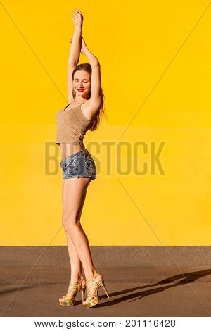 Very hot young freckled model beckoned you. Sensual brunette passionately closed eyes and hands up. Isolated on yellow background. Studio shot