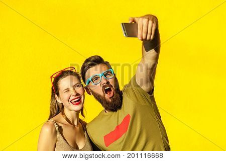 Hipsters couple macking selfie on yellow background. Studio shot