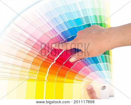 Person with a finger shows to the selected color in the palette for paint tinting. Colored catalog fan. The concept of choosing interior design