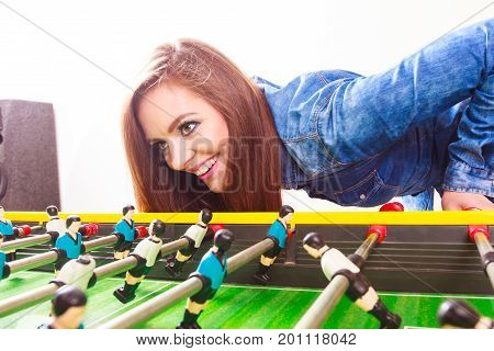 Play and fun concept. Young focused girl having fun with table soccer game. Fashionable woman playing spending free time on recreation.