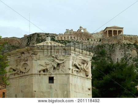 The impressive upper part of the Tower Of The Winds against the ancient Greek temple on the hilltop of Acropolis, Athens, Greece