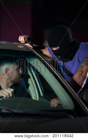 Closeup of dangerous criminal man with a gun in car parking. Auto theif threatening frightened driver, night time.