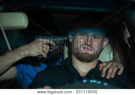Car thief threatening driver with the gun. Male robber wearing black mask sitting at the back seat and pointing gun at the head of scared owner