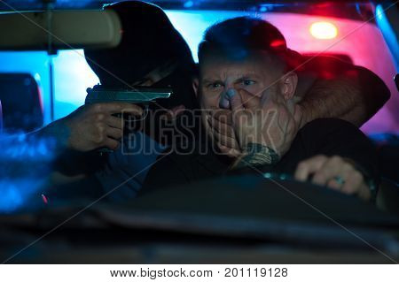 Dangerous car stealer pointing his gun at the car owner. Criminal man wearing black mask threatening driver and covering his mouth with hands. Police light on the background.