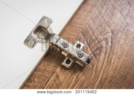 Door hinges at the cupboard on a wooden background