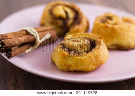 Cinnamon rolls and a pack of cinnamon sticks on pink plate ready to eat