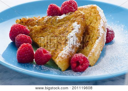 French toast with raspberries and honey on sky blue plate