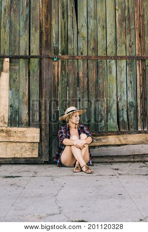 Farmer woman sitting at wooden barn door