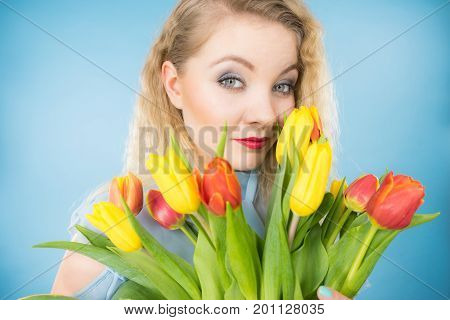 International womens day eight march. Beautiful portrait of pretty woman blonde hair with red yellow tulips fashion make up. Mothers day. On blue